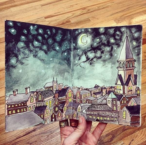 Sketchbook depicting inky night sky and drawn rooftops