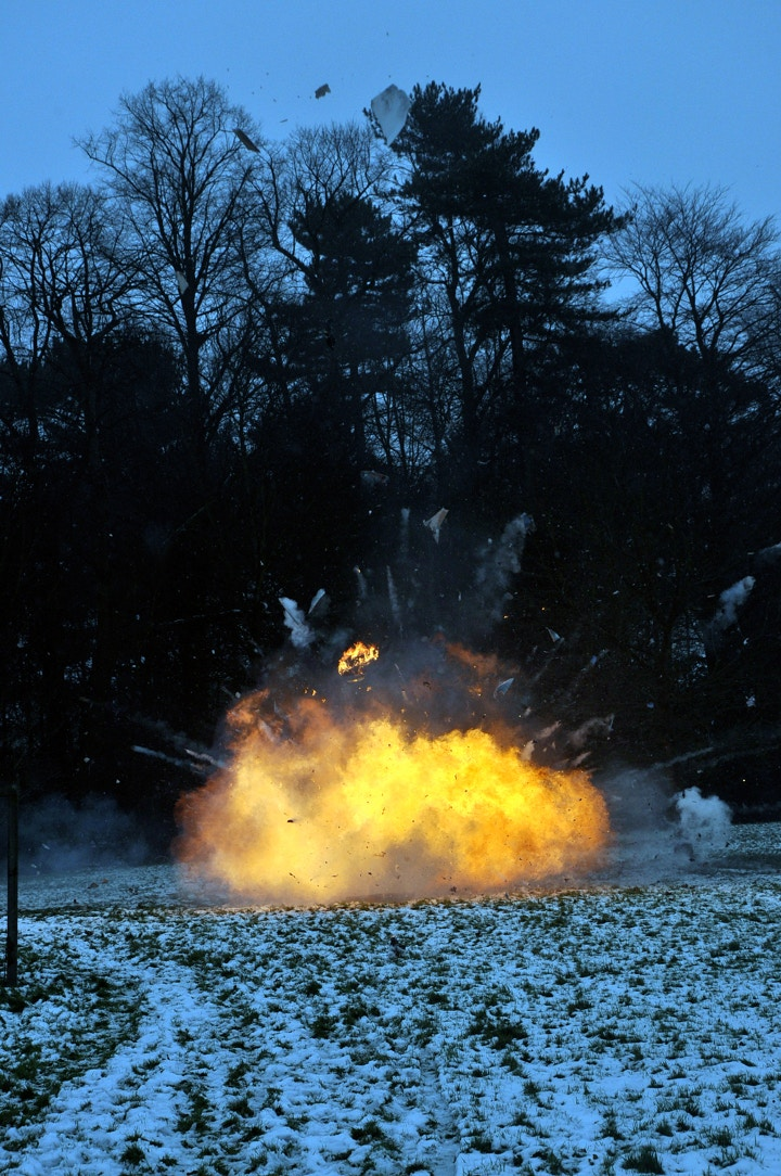 An explosion of one of Joe Steele's sculptures out in a forest