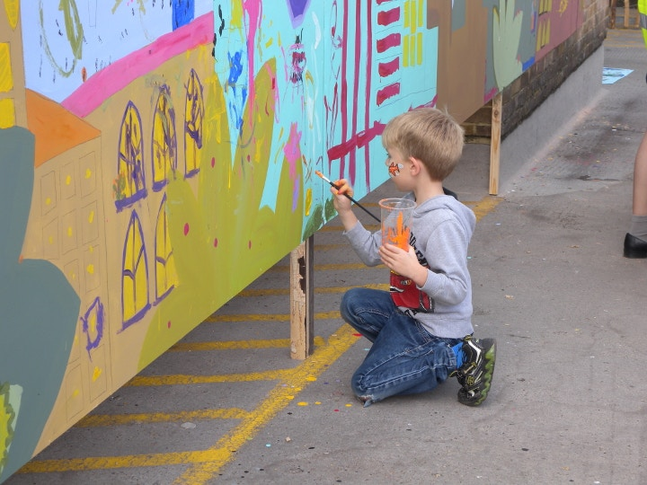 Young boy painting mural